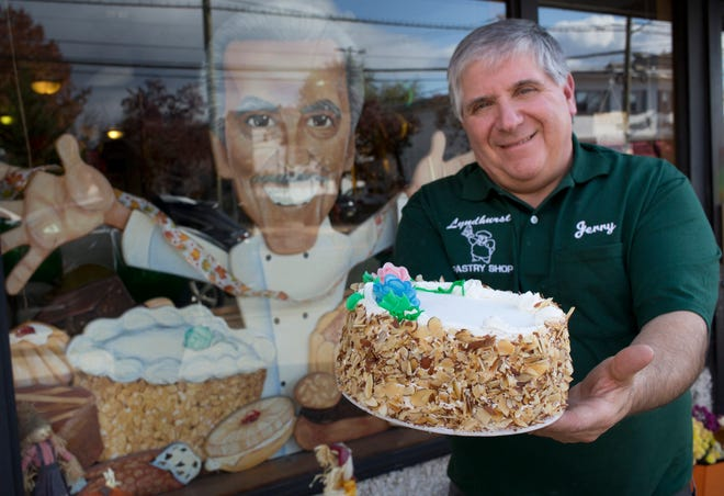 Jerry Lanzerotti Jr. holds out a rum cake in front of Lyndhurst Pastry Shop, which his dad and uncles started in 1948.   Erica Yoon/Special to NorthJersey.com
