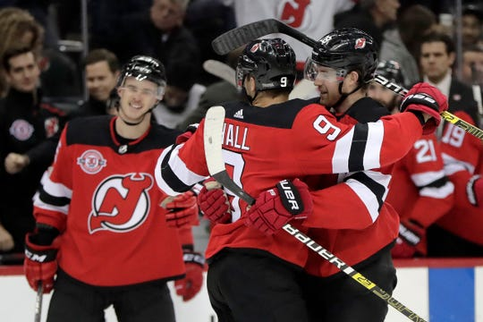New Jersey Devils defenseman Damon Severson, right, is congratulated by Taylor Hall, center, after he scored a goal during the second period of an NHL hockey game against the Pittsburgh Penguins, Tuesday, Nov. 13, 2018, in Newark, N.J.