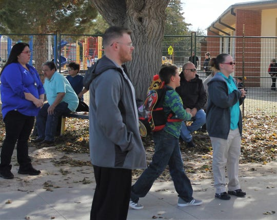 Parents wait to pickup their children at Heights Elementary after a water line break cause the school to cancel classes Wednesday afternoon.