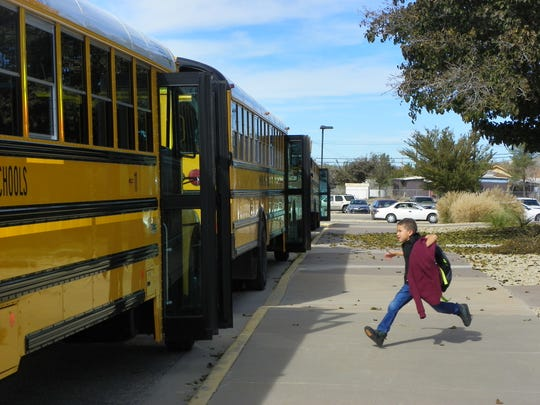 A Yucca Elementary student run to catch his bus after classes were temporarily cancelled due to a water line break near the school Wednesday.