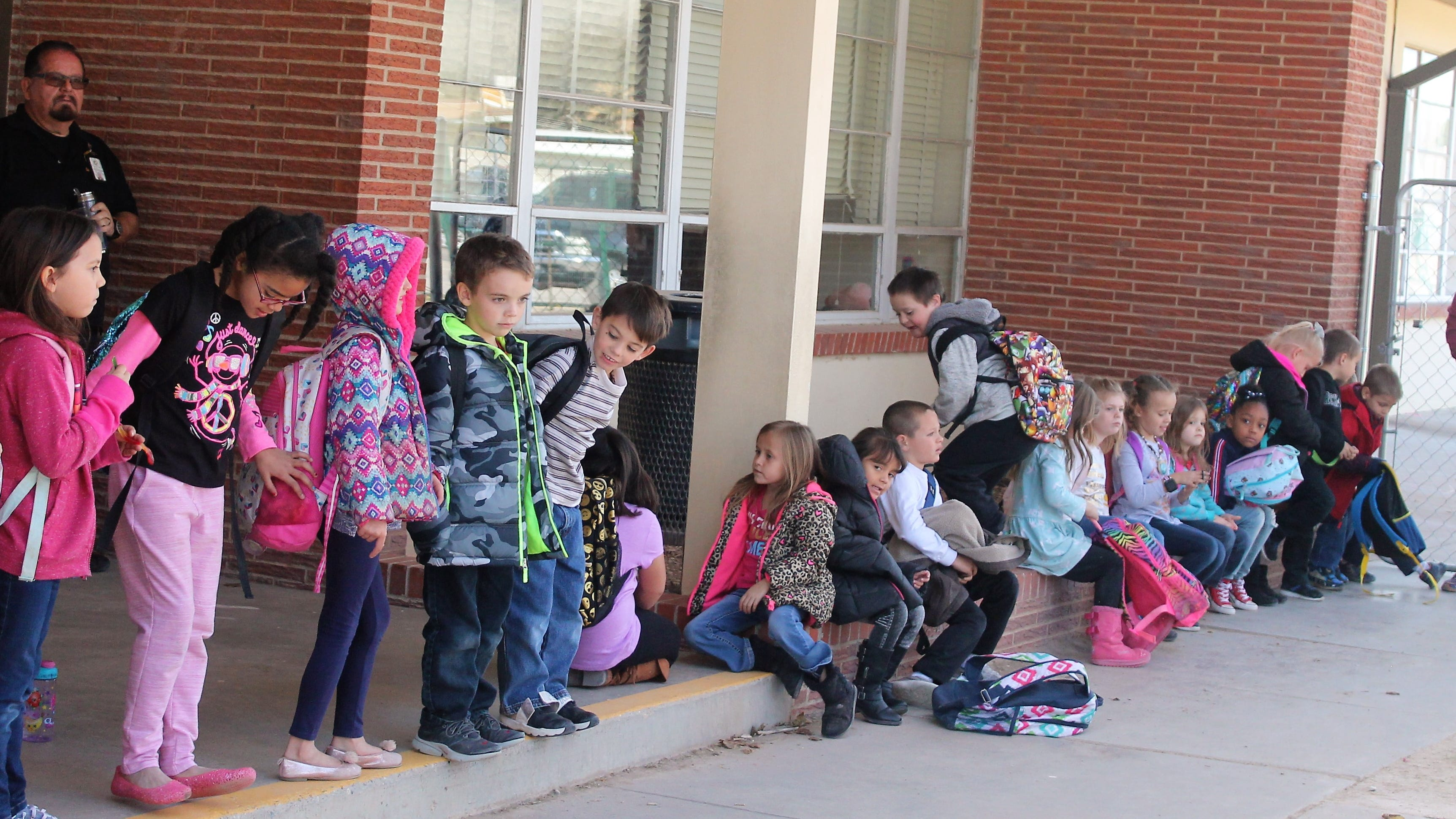 Students at Heights Elementary wait for rides home after a water main break and water outage at Heights Elementary caused students to be released early. The outage also caused Yucca Elementary students to be released early.