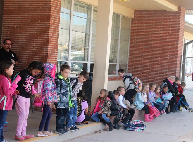 Heights Elementary students wait for a ride home after a water main break near the school caused students to be released from class early Wednesday afternoon.