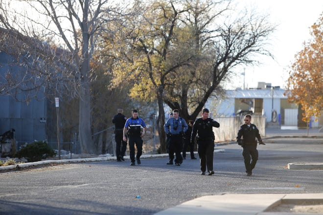 Officers for the Farmington Police Department investigate the parking lot of the building located at 101 W. Animas St. on Wednesday afternoon where three people were stabbed by a male suspect. The suspect is in police custody.