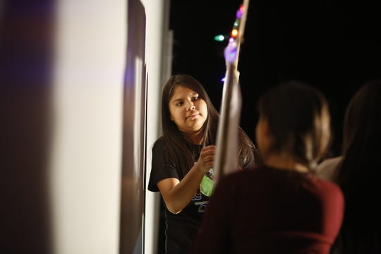 Tsé Bit A'í Middle School eighth-grader Khloe Henderson adjusts string lights attached to a prop during a rehearsal on Tuesday at the Phil L. Thomas Performing Arts Center in Shiprock.