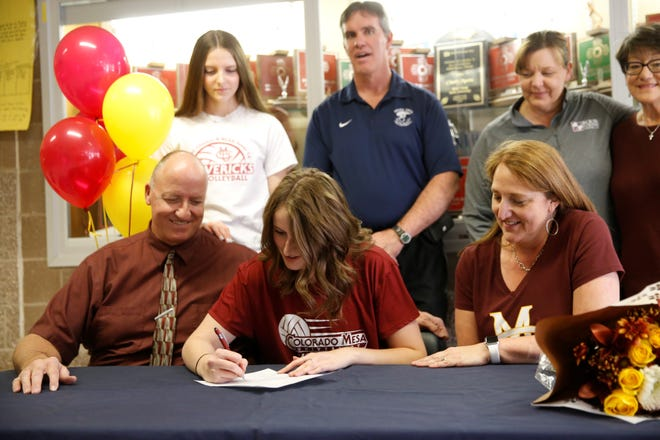 Piedra Vista middle blocker Courtney Moore signs her letter of intent on Wednesday to continue her volleyball career at Colorado Mesa University.