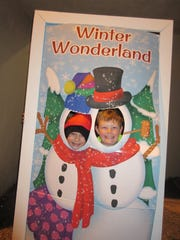 Two children take opportunity of a photo opp at Christmas in the Park 2017, pretending to be snowmen.