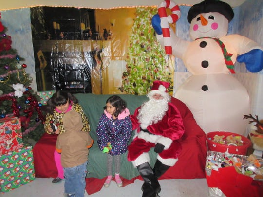 Three children play with their gifts from Santa Claus at Christmas in the Park 2017.