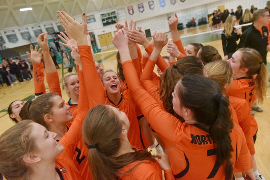 Northville players celebrate after a three-set victory over Livonia Churchill in the Division 1 girls volleyball quarterfinal at Ann Arbor Huron.