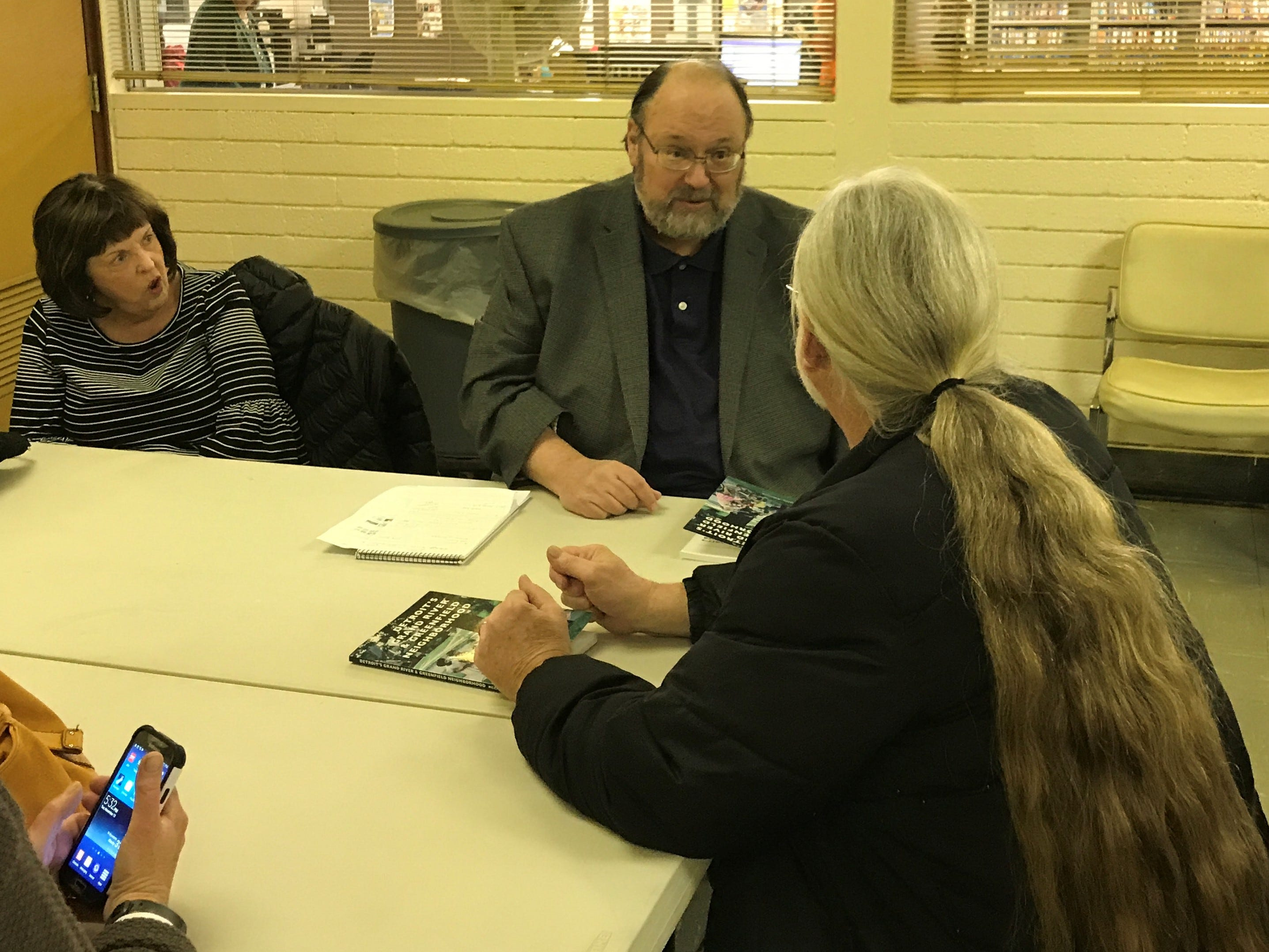 Author Joseph McCauley, of Northville talks with Steve Backus (right) about the Detroit neighborhood his book is about. At left is McCauley's wife, Grace.