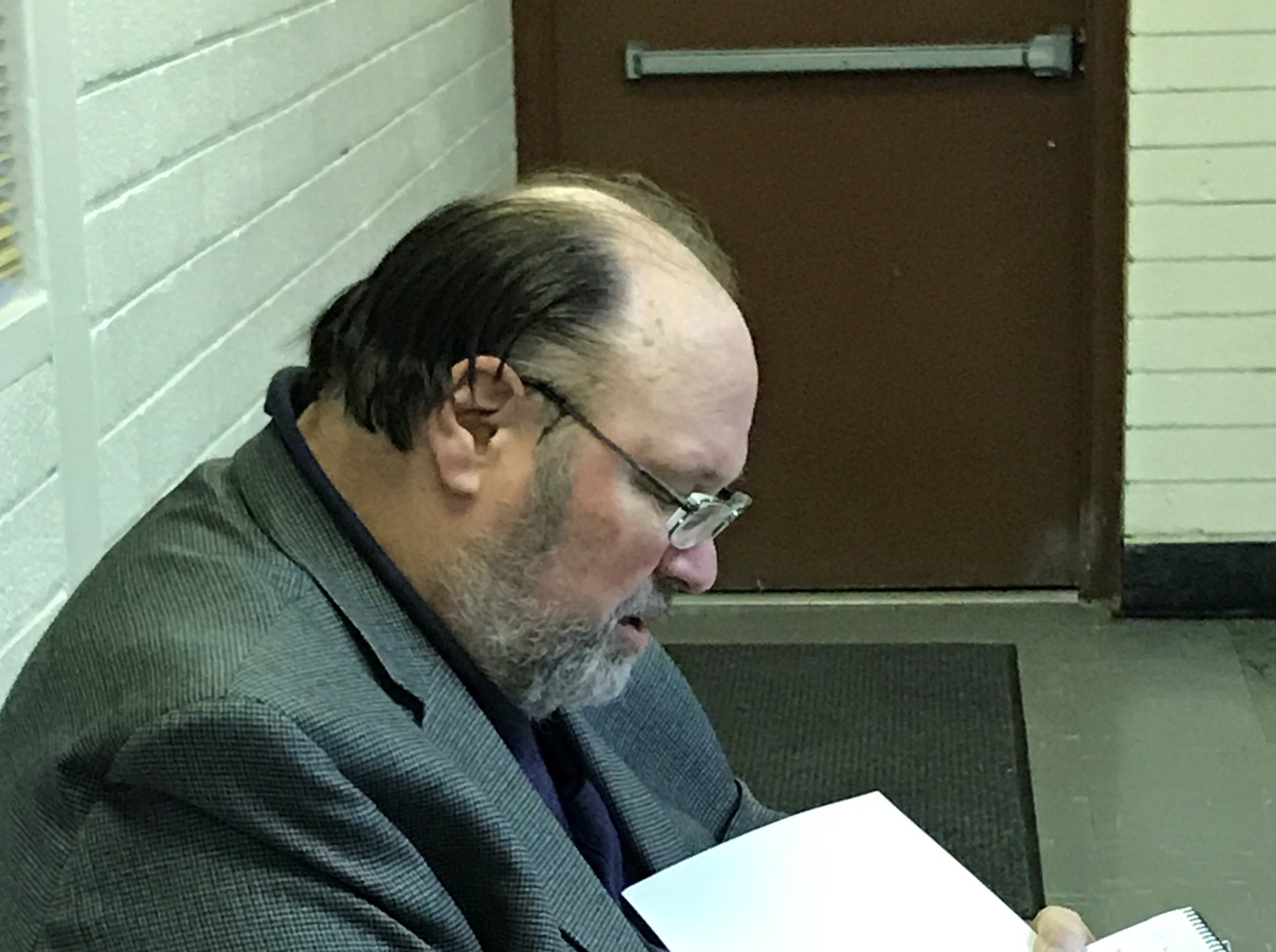 Author Joseph McCauley, of Northville, signs a copy of his new book following Tuesday's discussion.