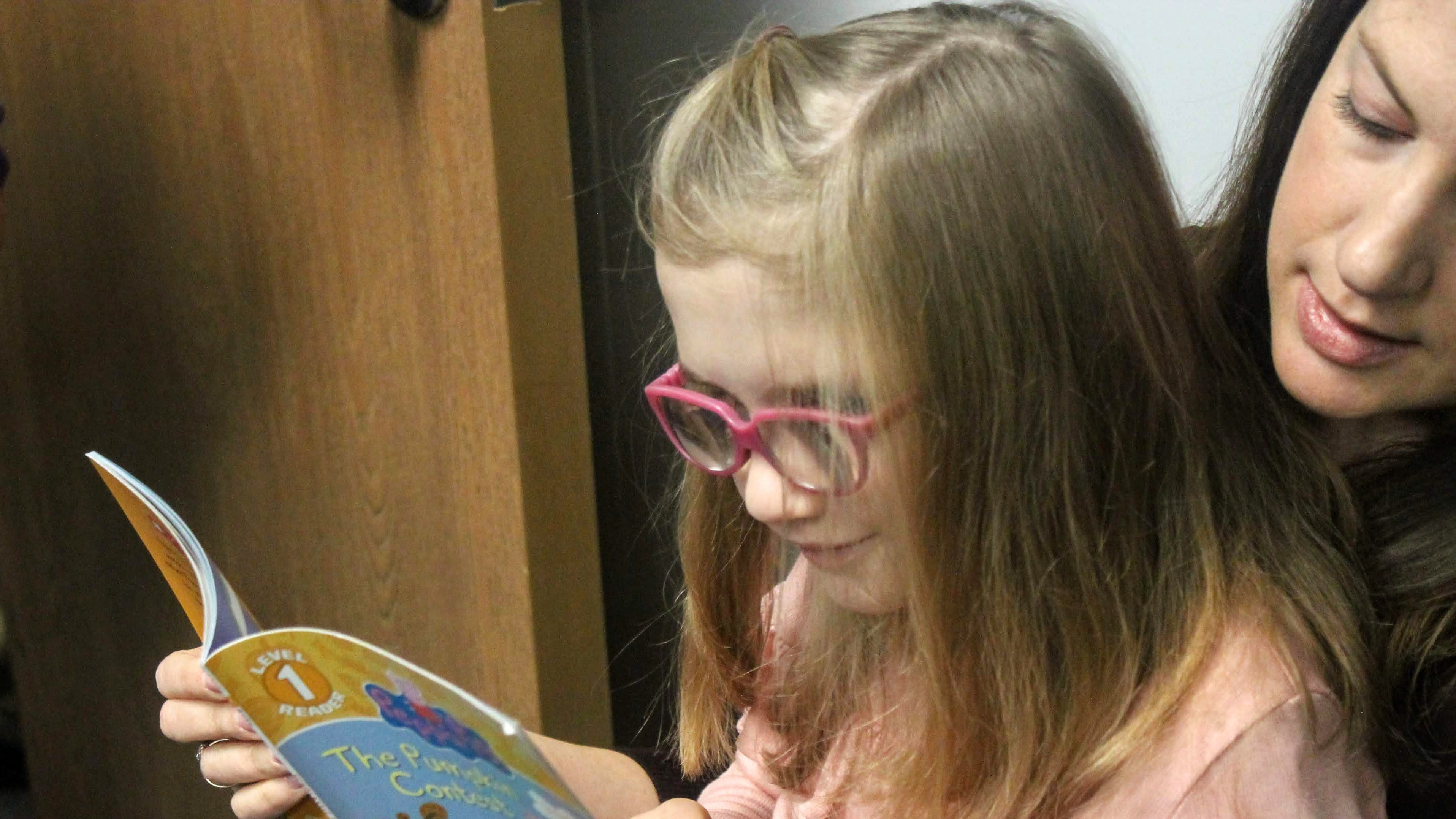 Avery Devereux, 8, reads with her mother, Ann Devereux, at Seedlings Braille Books for Children. The Devereux's live in Royal Oak.D