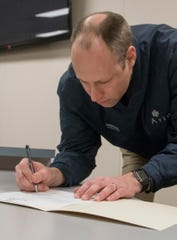 City Councilman Phillip Wagner signs paperwork after being sworn in.