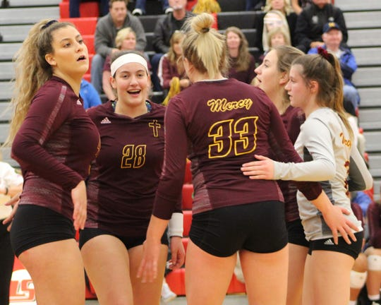 Mercy players celebrates a point in the 2018 Division 1 state quarterfinal volleyball victory over Sterling Heights Stevenson at St. Clair Shores South Lake High School.