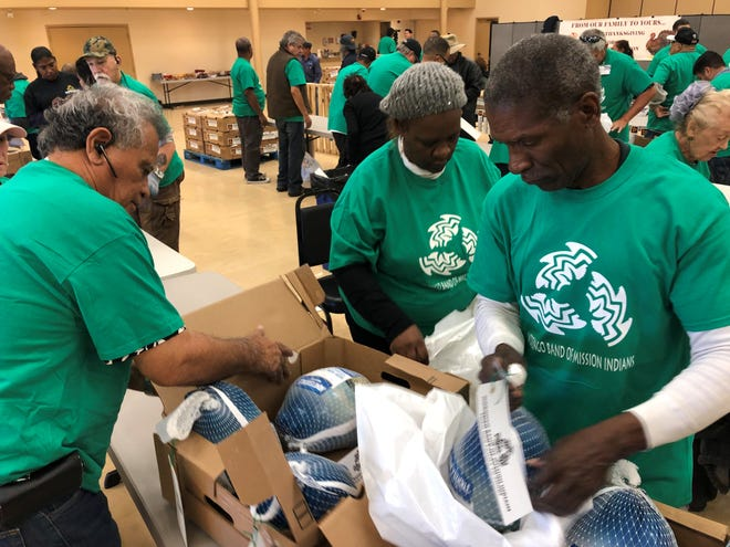 Volunteers on Wednesday sort and package frozen turkeys to be donated to families in need by the Morongo Band of Mission Indians.