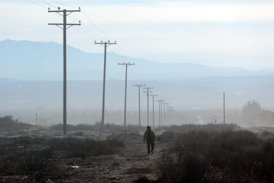 A member of the fire crew working in the Sierra Fire walks along N. Riverside Avenue in between Alder Avenue and Sierra Avenue in Rialto as the Santa Ana winds blow smoke and dust on Wednesday, November 14, 2018.