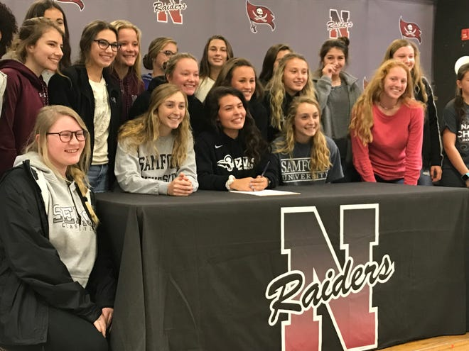 Navarre girls soccer players Anakah Madril (middle table) and Jennifer Seward (right at table) celebrate with teammates after signing with University of Mobile and Division I Samford respectively on Wednesday.