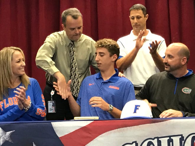 Pace High senior pitcher Brandon Sproat is joined by his family, mother Carolina and father John, along with Pace principal Stephen Shell (back left) and baseball coach Jason McBride during Wednesday's signing ceremony after Sproat signed with Florida.