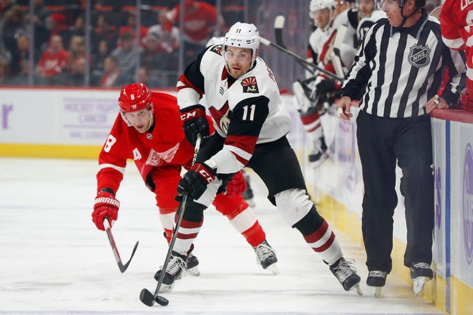 Arizona Coyotes left wing Brendan Perlini (11) carries the puck up ice from Detroit Red Wings left wing Justin Abdelkader (8) in the first period of an NHL hockey game Tuesday, Nov. 13, 2018, in Detroit.