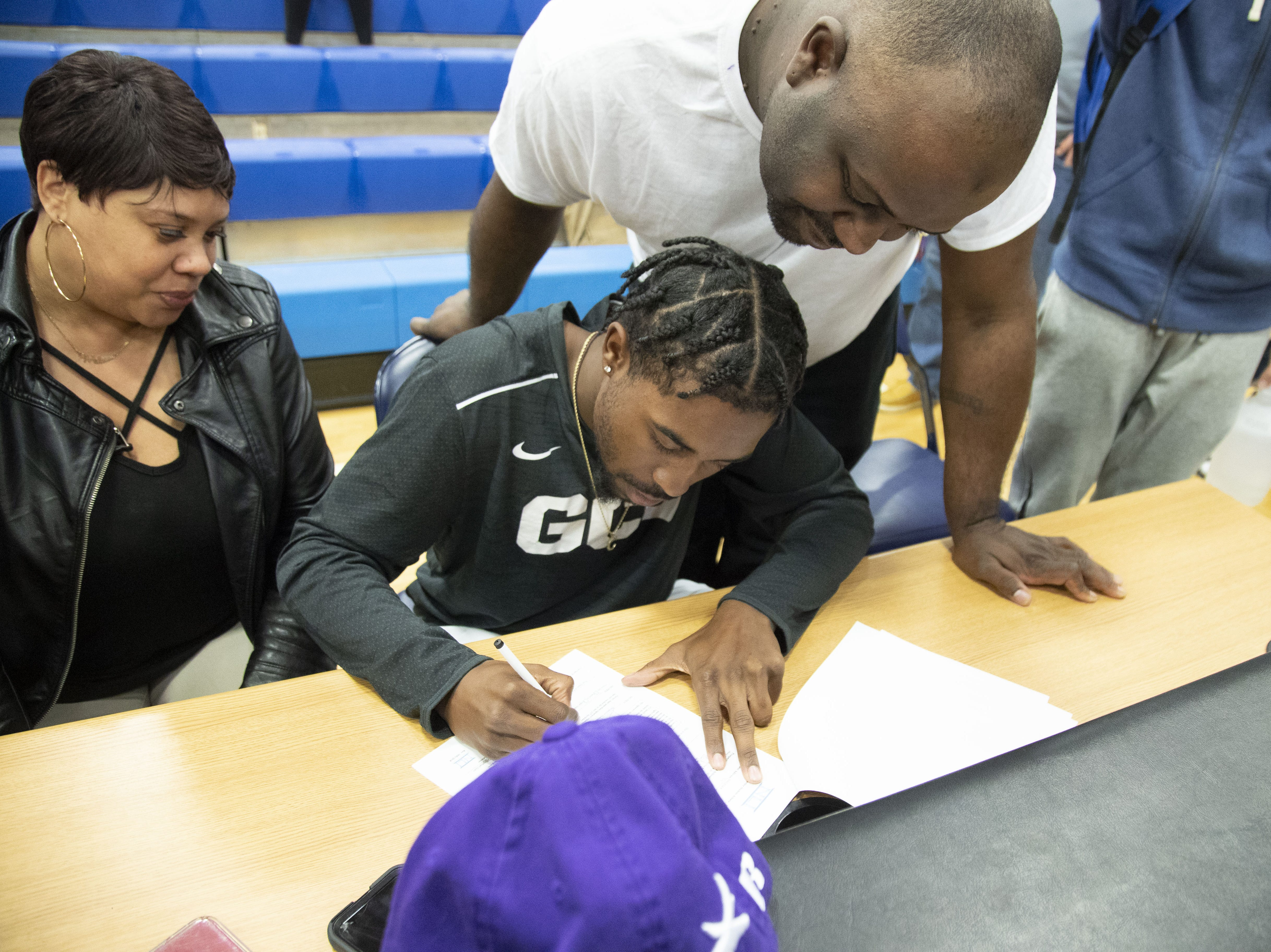 Shadow Mountain's Jovan Blacksher with his father Jovan Blacksher Sr. and mother Lashaun James during a signing ceremony at the school gym. Jovan signed with Grand Canyon.