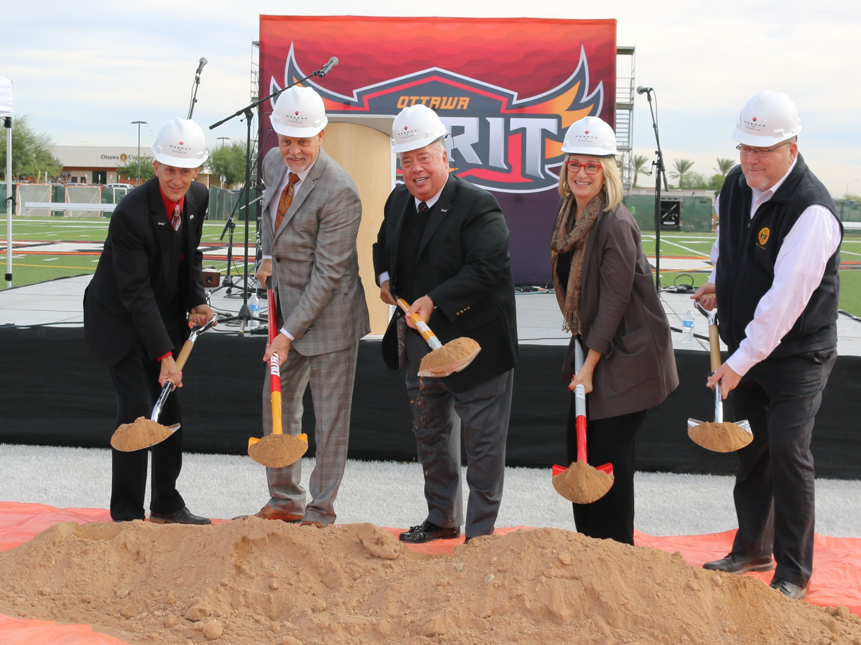 Officials toss dirt at the groundbreaking for Ottawa University's residence hall in Surprise.