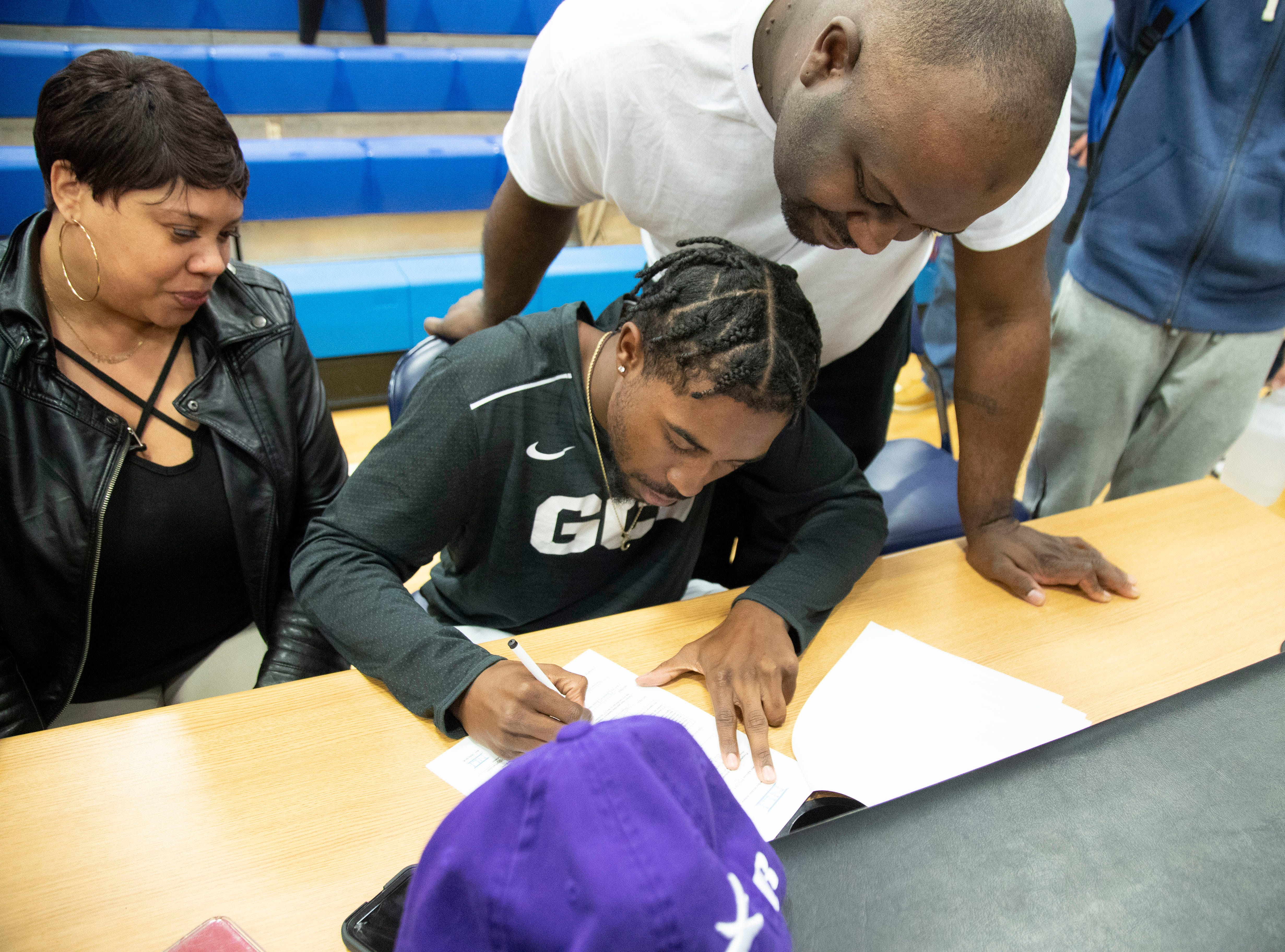 Shadow Mountain High School senior Jovan Blacksher signs with GCU as his father Jovan Blacksher Sr. and mother Lashaun James look on at the gym on Nov. 14, 2018.