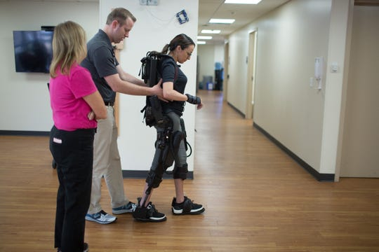 Jovanna Calzadillas walks with the help of an exoskeleton at the Barrow Center for Transitional Neuro- Rehabilitation.