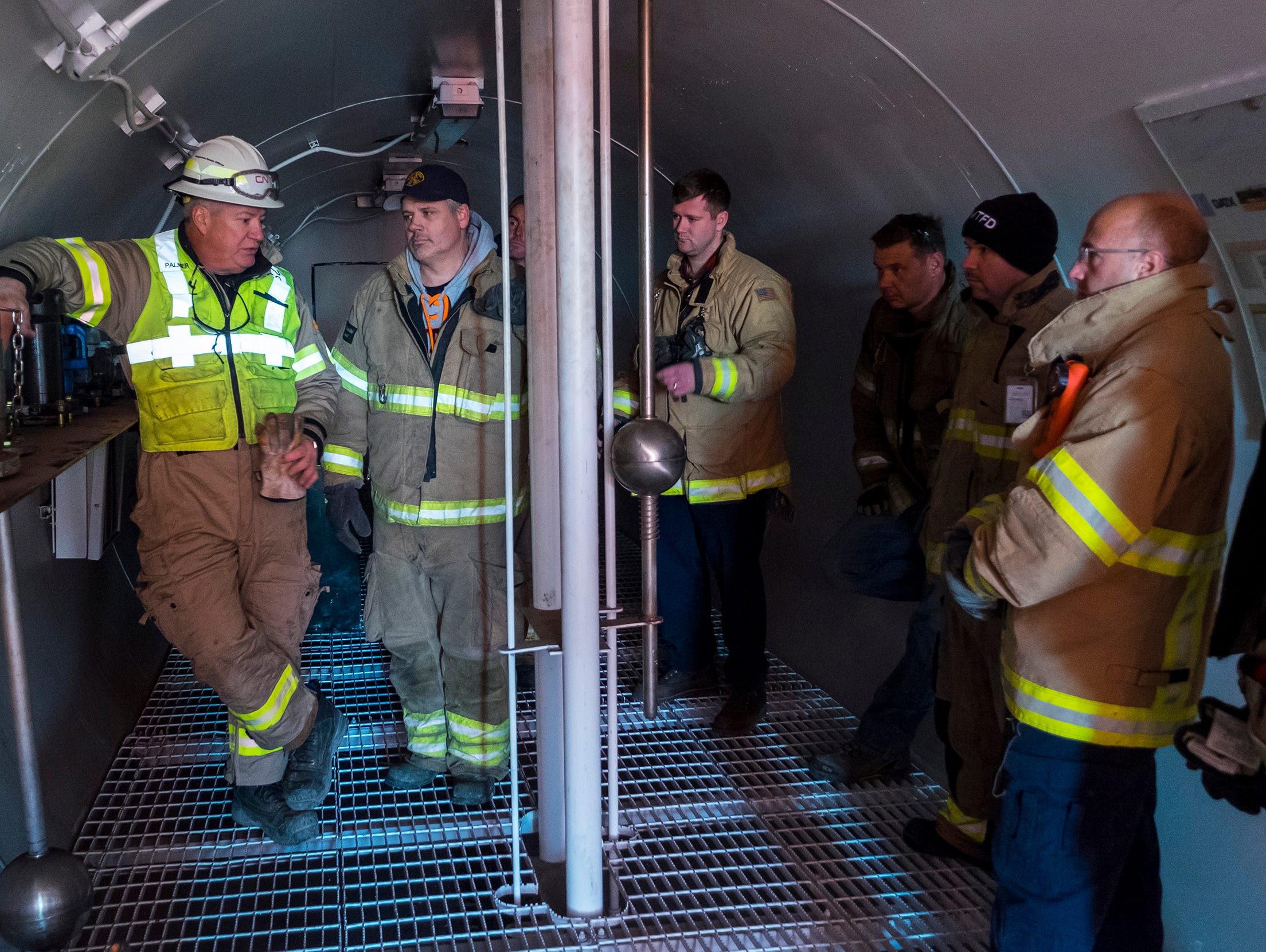 Greg Palmer, CN Rail dangerous goods officer, left, talks to a group of firefighters about different pressure release valves inside a CN Rail tank car during a hazardous materials training class Wednesday, Nov. 14, 2018 at the CN Rail yard in Port Huron.