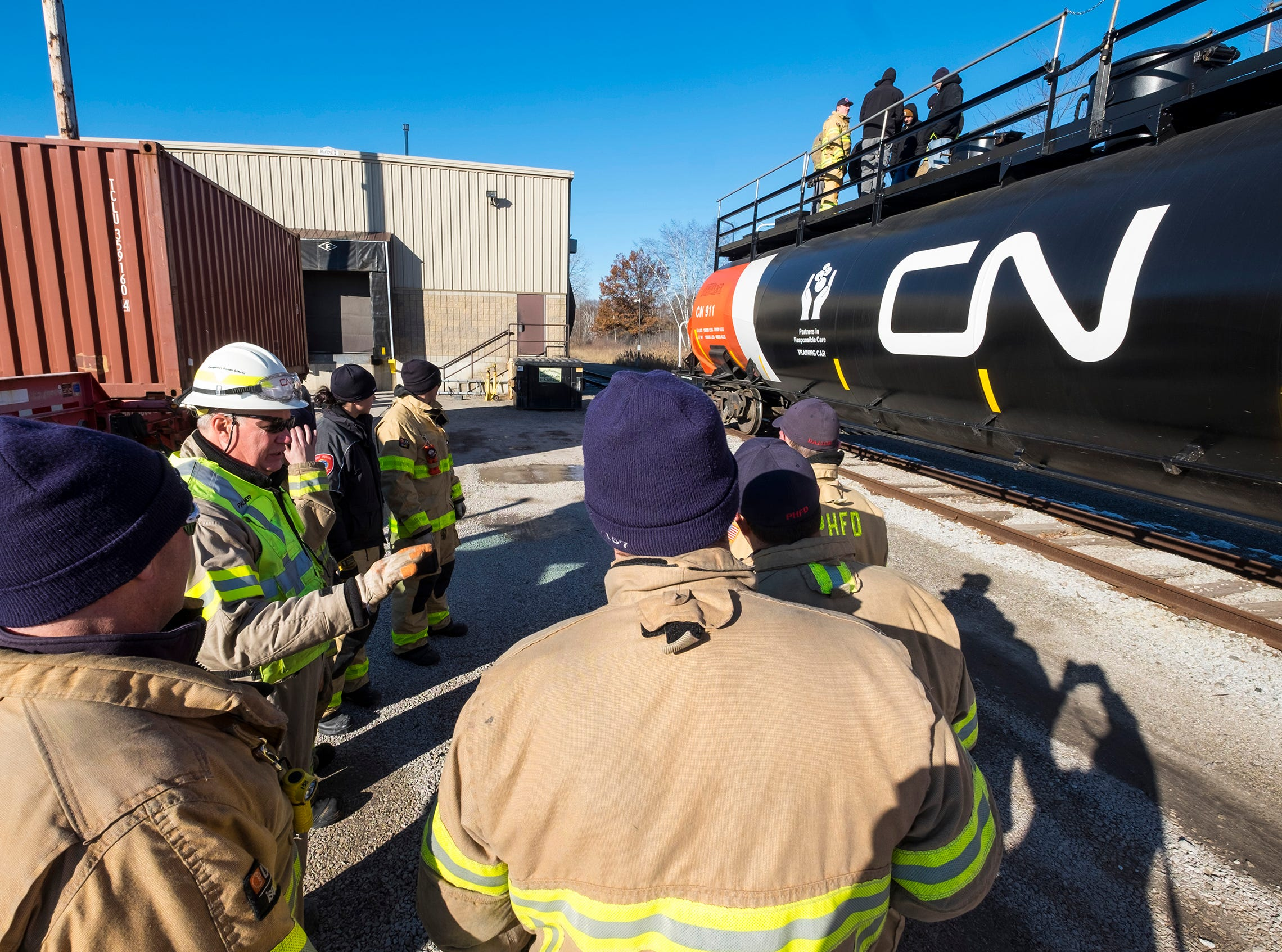 CN Rail Dangerous Goods Officer Greg Palmer, left, talks about the different markings on the side of a CN Rail tank car with area firefighters during a hazardous materials training session Wednesday, Nov. 14, 2018 at the CN Rail yard in Port Huron.