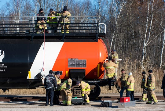 Firefighters climb on a CN Rail tanker car during a hazardous materials training class Wednesday, Nov. 14, 2018 at the CN Rail yard in Port Huron.