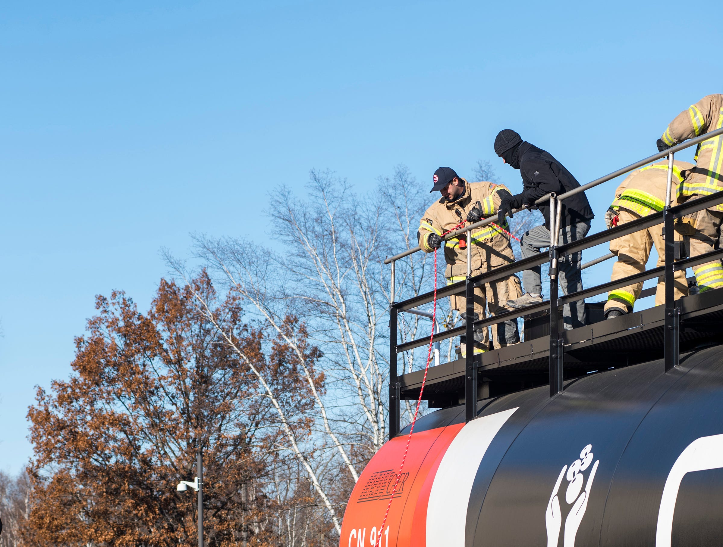Port Huron Firefighter Peter Lafata, top, lowers a bucket of tools down the side of a CN Rail tank car to Clinton Township Firefighter Terry Hollstein during a hazardous materials training Wednesday, Nov. 14, 2018 at CN Rail yard in Port Huron.