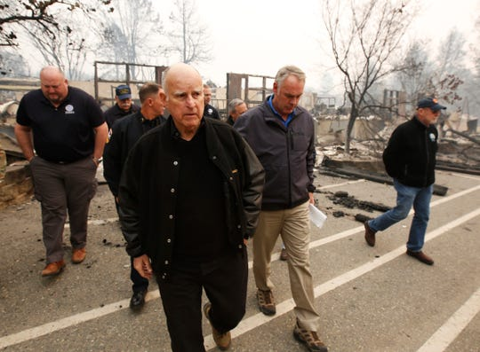California Gov. Jerry Brown, center, and Interior Secretary Ryan Zinke, second from right, tour the fire ravaged Paradise Elementary School Wednesday, Nov. 14, 2018, in Paradise, Calif. The school is among the thousands of homes and businesses destroyed along with dozens of lives lost when the fire burned through the area last week. (AP Photo/Rich Pedroncelli)