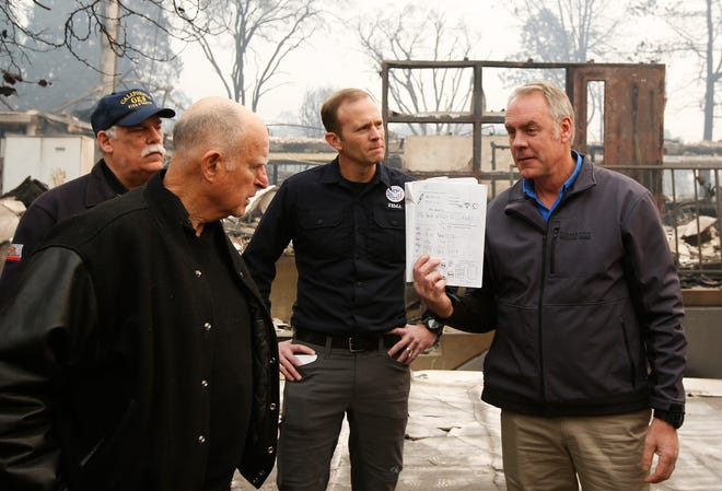 California Gov. Jerry Brown, second from left, looks at a students work book displayed by Interior Secretary Ryan Zinke, that was found during a tour of the fire ravaged Paradise Elementary School Wednesday, Nov. 14, 2018, in Paradise, Calif. The school is among the thousands of homes and businesses destroyed along with dozens of lives lost when the fire burned through the area last week. (AP Photo/Rich Pedroncelli)