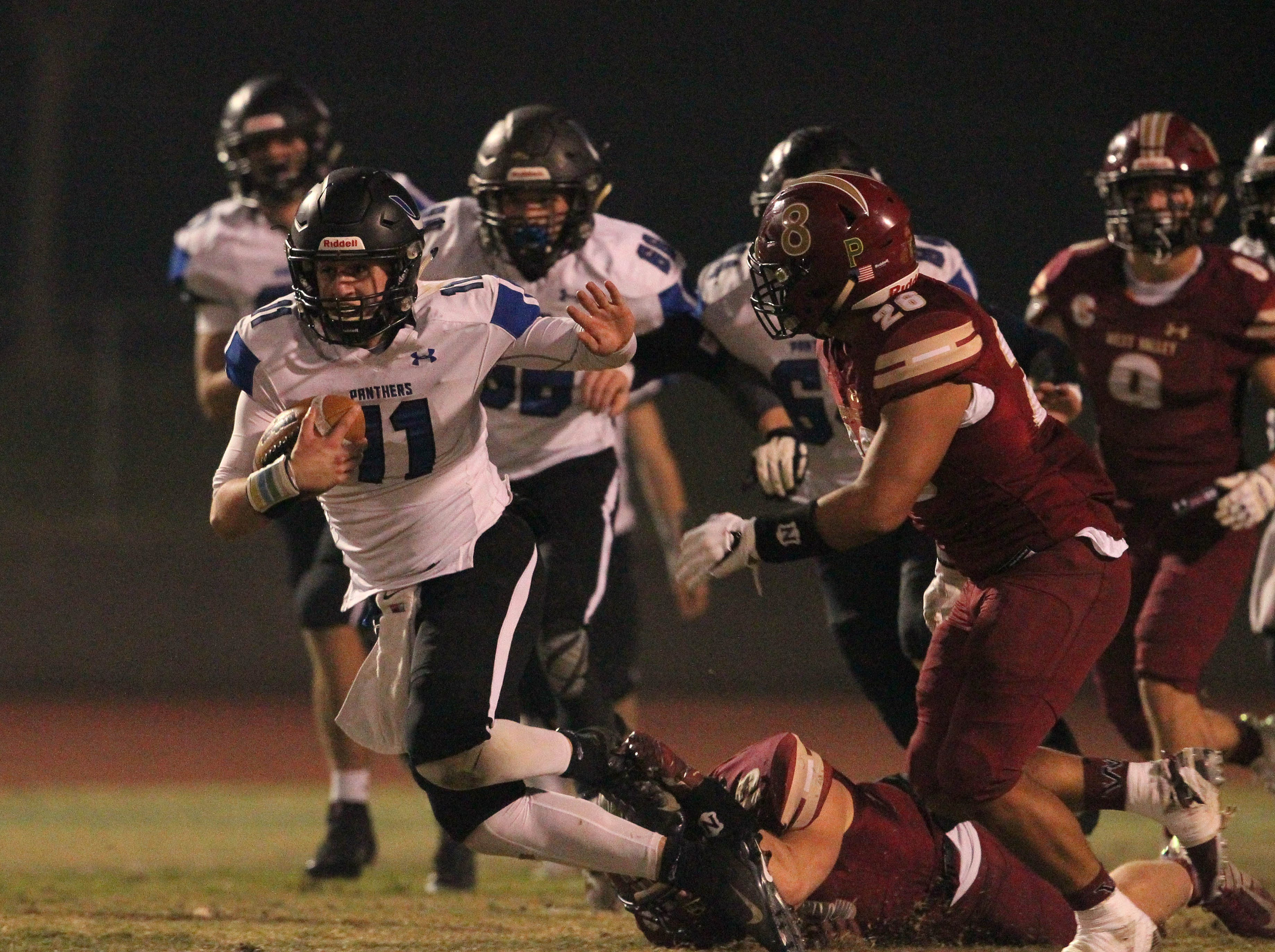 U-Prep QB Dylan Cabral (11) tries to run for a first down against West Valley's Bailey Sulzer (13) and Joshua Aguilar (26) in the 3rd quarter on Friday, Nov. 9.  The Eagles defeated the Panthers, 55 -6, at home to advance to the 2nd round against Lassen on Nov. 16.