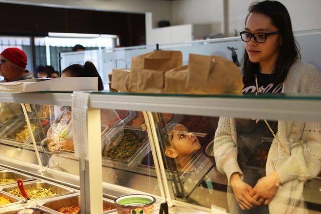 Darla Torres looks up at her mother, Cecelia, as Torres orders burritos at El Charrito.
