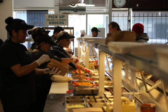 Workers throw together burritos in record time for customers at El Charrito in Salinas.