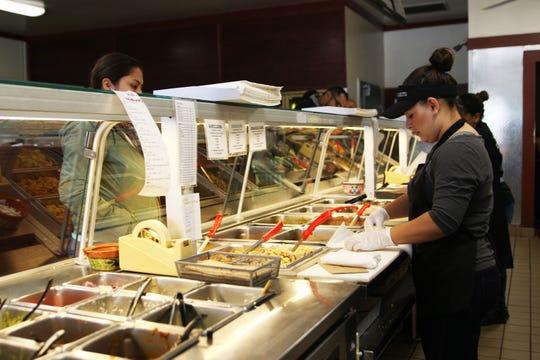 Los trabajadores producen burritos en tiempo récord para los clientes de El Charrito.