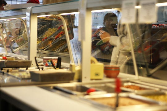 A woman watches workers through the glass at El Charrito.
