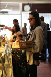 Darla Torres peeks over the edge of the box of burritos her mother, Cecelia Torres, holds.