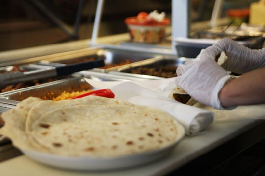 A worker rolls a burrito for a customer at El Charrito.