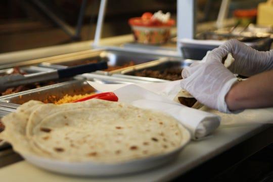 A worker rolls a burrito for a customer at El Charrito.