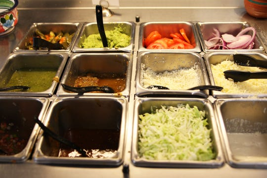 Toppings sit in containers, waiting to be eaten, at El Charrito.