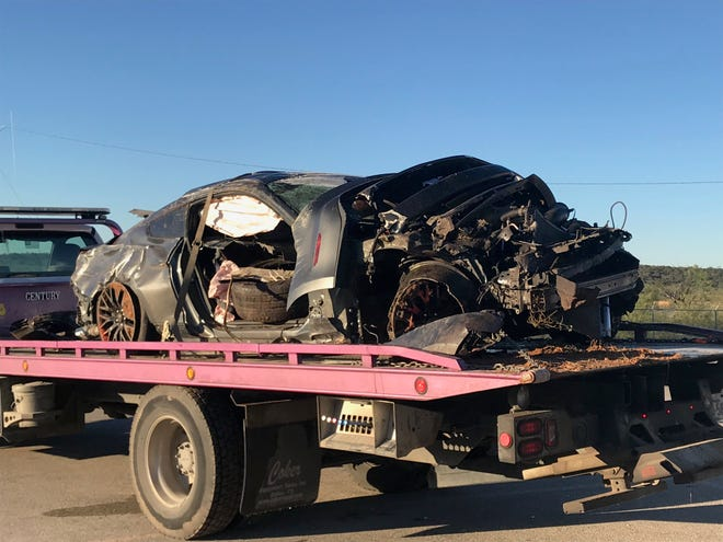 A 2016 Mustang is towed off in the 6000 block of Knickerbocker on Tuesday, Nov. 14, 2018. The car hit a pole, flipped several times and landed in an embankment.