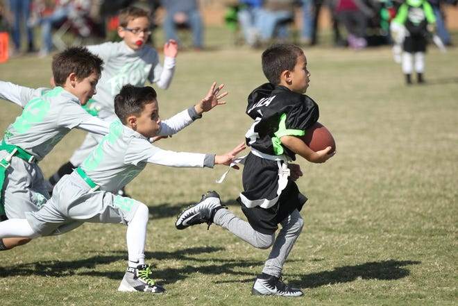 Elijah Loza runs past Ryker White (12) and Adrian Esparza (15) during the 2018 flag football tournament at Texas Bank Sports Complex. Registration for the 2019 Flag Football league is open until Aug. 9.