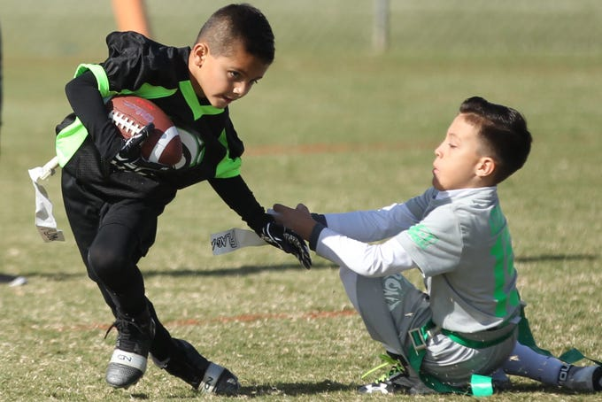 San Angelo Seahawks' Aiden Reyes tries to shake off The Front's Adrian Esparza during the championship game of the 6u TAAF State Youth Flag Football Tournament at the Texas Bank Sports Complex on Sunday, Nov. 11, 2018. The Front won a defensive battle 13-0.