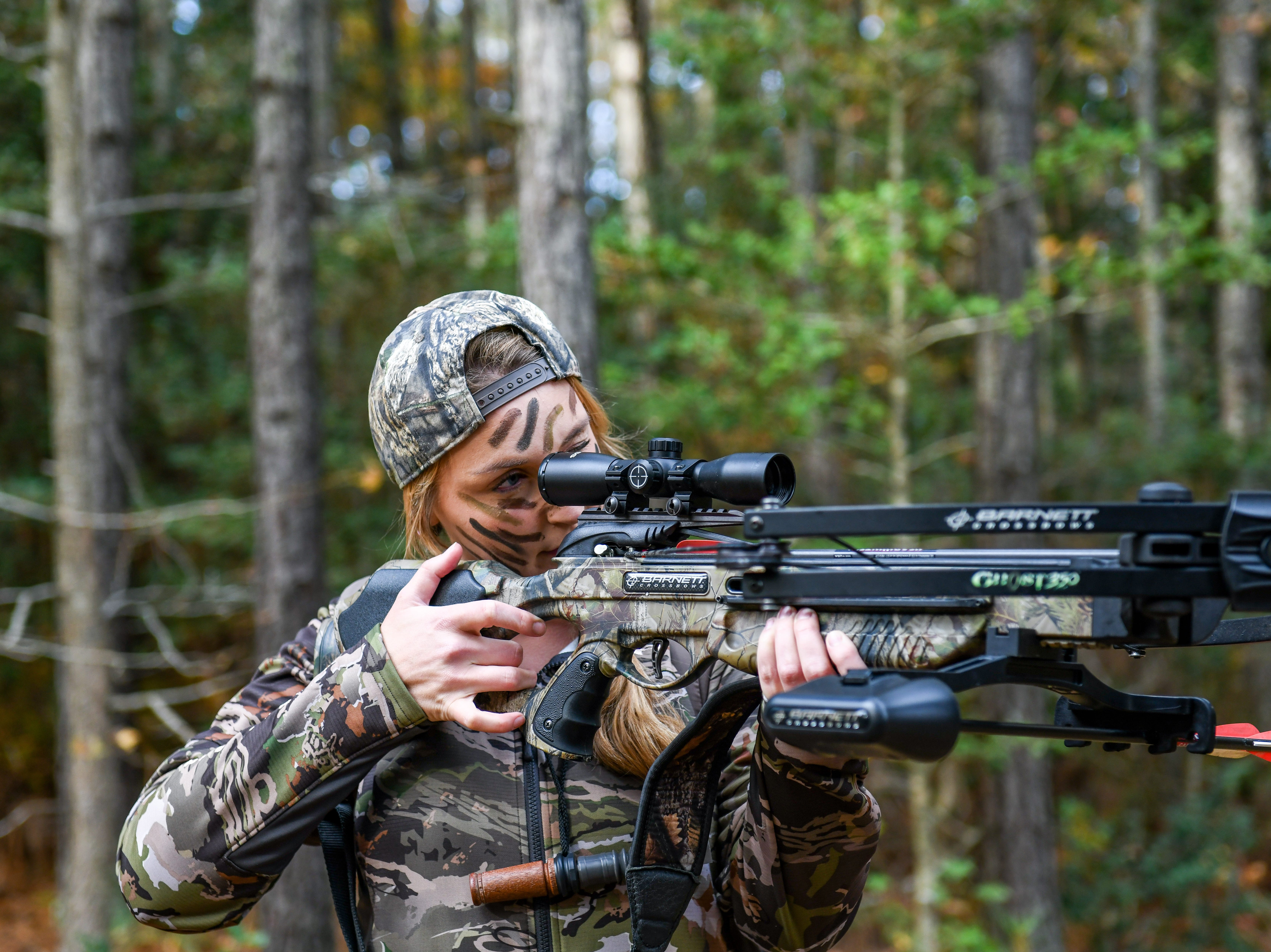 Fidelia Kurtz looks through her scope for deer in the woods on the way out to her hunting stand in Snow Hill on Thursday, Nov 8, 2018.