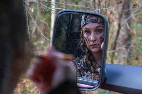 28-year-old Fidelia Kurtz applies face paint in her truck as she prepares to go hunting in Snow Hill on Thursday, Nov 8, 2018.