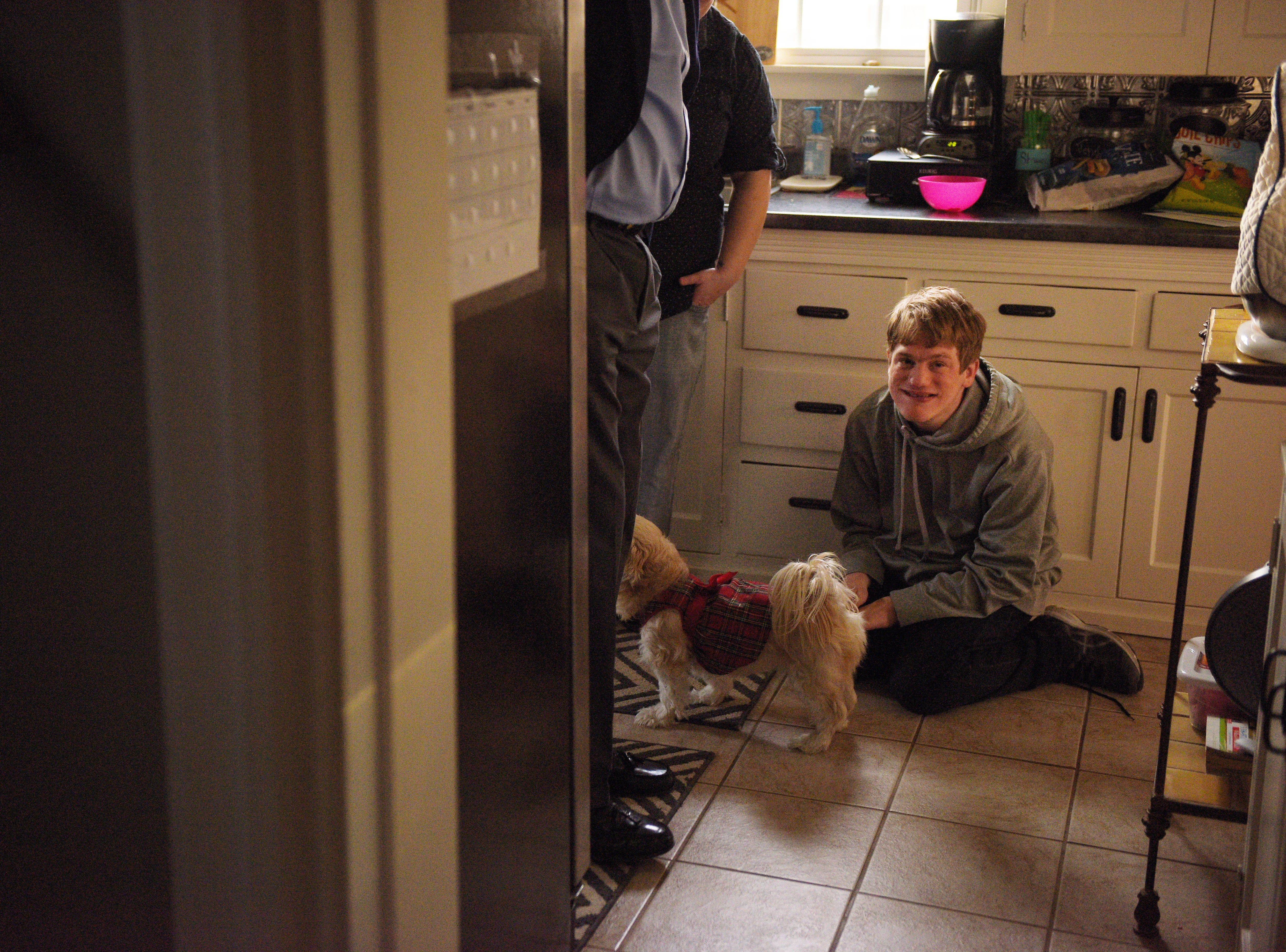 Ben Graff sits on his kitchen floor as his family comes into his new home Wednesday, Nov. 7, in Sioux Falls. He lives with Shared Living Provider Kayla Harris and roommate Jenna Askelson. Graff is now able to live independently from his parents with the assistance of Shared Living.