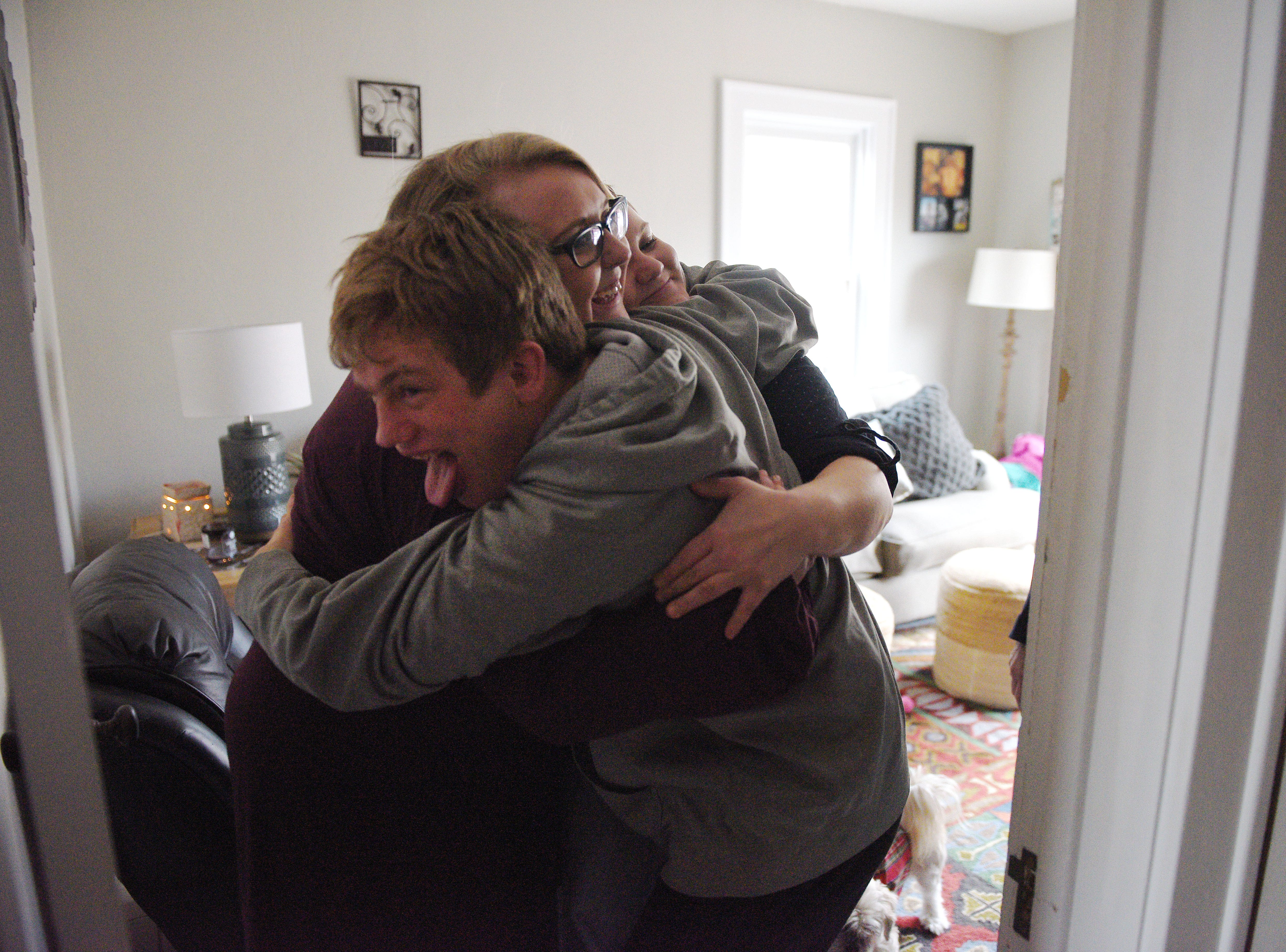 Ben Graff gives a hug to his roommates Kayla Harris and Jenna Askelson Wednesday, Nov. 7, at their house in Sioux Falls. Harris is able to care for Ben by being a Shared Living Provider.