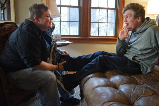 Shared Living Provider Kayla Harris puts Ben Graff's shoe back on for him at his new house Wednesday, Nov. 7, in Sioux Falls. He lives with Shared Living Provider Kayla Harris and roommate Jenna Askelson.