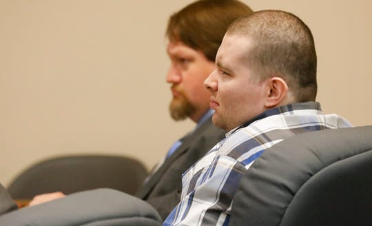 """Nicholas Godejohn, 29, who is charged with first-degree murder in the June 2015 killing of 48-year-old Clauddine """"Dee Dee"""" Blanchard, squints to read text messages presented as evidence on the second day of his trial on Wednesday, Nov. 14, 2018."""